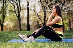 健身美丽的妇女坐席子为室外的锻炼做准备 图库摄影
