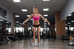 健身美丽的妇女执行与扩展器的锻炼在健身房 免版税库存照片