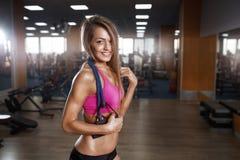 健身美丽的妇女执行与扩展器的锻炼在健身房 免版税库存图片