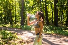 健身美丽的妇女饮用水和冒汗在行使以后在夏天热的天在公园 以后女运动员 免版税库存图片