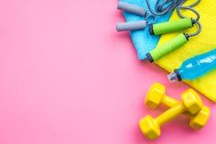 健身背景 健身房和家的设备 跳绳,哑铃,扩展器,在粉红彩笔背景顶视图的水 库存照片