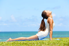 健身舒展在眼镜蛇姿势的瑜伽妇女 库存照片