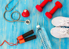 健身设备健身房锻炼和淡水与心脏和医疗听诊器在蓝色背景 免版税库存图片
