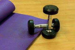 健身设备哑铃,瑜伽席子,在木背景 免版税库存照片