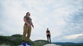 健身辅导员在一座低山站立并且享受美丽的景色 股票视频