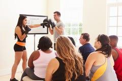 健身辅导员对超重人民演讲在饮食俱乐部 免版税库存图片