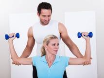 帮助妇女锻炼的健身辅导员 免版税库存照片
