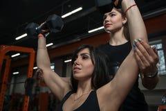 健身辅导员帮助的女孩 图库摄影
