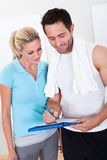 采取笔记的健身辅导员在会议以后 免版税库存照片