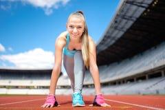 健身运动女孩为在体育轨道的奔跑做准备在体育场 与女孩赛跑的健康和运动的生活方式 库存图片