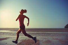 健身运行在日出海滩的妇女赛跑者 库存图片