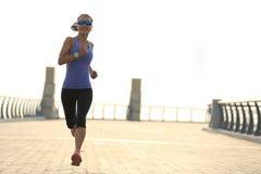 健身运行在海边桥梁的妇女赛跑者 库存图片