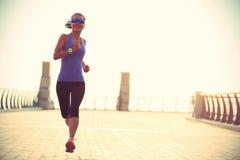健身运行在海边桥梁的妇女赛跑者 图库摄影