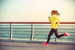 健身运行在海边的妇女赛跑者 图库摄影
