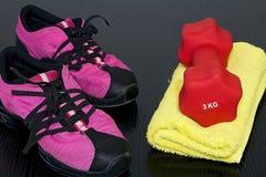 健身鞋子和毛巾与哑铃在船上 免版税图库摄影