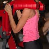 健身,体育和行使概念:做蹲坐用健身房设备的运动服的女孩 免版税库存照片
