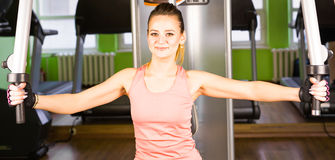 健身,体育,电源举和人概念-修造在模拟器的运动的女孩有些肌肉 图库摄影