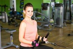 健身,体育,电源举和人概念-修造在模拟器的运动的女孩有些肌肉 库存照片