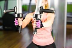 健身,体育,电源举和人概念-修造在模拟器的运动的女孩有些肌肉 免版税图库摄影