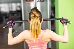 健身,体育,电源举和人概念-修造在模拟器的运动的女孩有些肌肉 免版税库存图片
