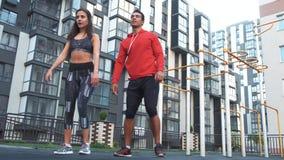 健身,体育,行使和健康生活方式概念-做蹲坐的男人和妇女户外在城市 影视素材