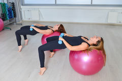 健身,体育,行使生活方式-做与哑铃和适合ballsin的小组妇女锻炼普拉提类在 免版税库存照片