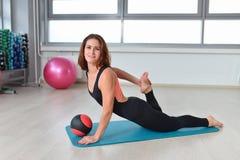 健身,体育,行使生活方式-做舒展的适合的妇女在健身房行使 免版税图库摄影