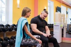 健身,体育,行使,技术和饮食概念-微笑的少妇和个人教练员与片剂个人计算机 免版税库存图片