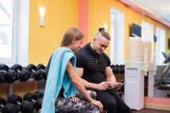 健身,体育,行使,技术和饮食概念-微笑的少妇和个人教练员与片剂个人计算机 库存图片