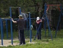健身,体育,行使,训练和生活方式概念-做三头肌的年轻人在双杠浸洗户外 免版税库存照片