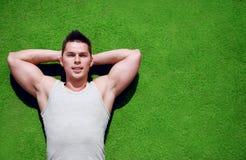 健身,体育-概念 放松在草的英俊的人 免版税库存图片
