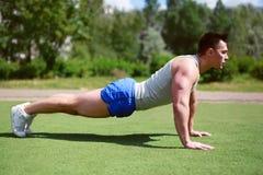 健身,锻炼,体育-概念 运动员俯卧撑 免版税库存图片