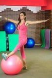 健身 一套桃红色体育衣服的年轻美丽的白女孩做与一个桃红色适合球的体育运动在健身中心 库存照片