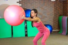 健身 一套桃红色体育衣服的年轻美丽的白女孩做与一个桃红色适合球的体育运动在健身中心 库存图片