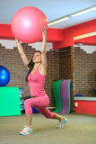 健身 一套桃红色体育衣服的年轻美丽的白女孩做与一个桃红色适合球的体育运动在健身中心 图库摄影