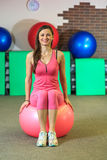 健身 一套桃红色体育衣服的年轻美丽的白女孩做与一个桃红色适合球的体育运动在健身中心 免版税库存照片