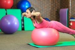 健身 一套桃红色体育衣服的年轻美丽的白女孩做与一个桃红色适合球的体育运动在健身中心 免版税库存图片