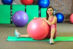 健身 一套桃红色体育衣服的年轻美丽的白女孩做与一个桃红色适合球的体育运动在健身中心 免版税图库摄影
