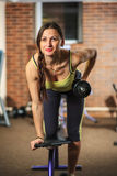健身 一套黄色和灰色体育衣服的年轻美丽的白女孩做着与一个哑铃的锻炼在训练用具 免版税图库摄影
