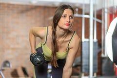 健身 一套黄色和灰色体育衣服的年轻美丽的白女孩做着与一个哑铃的锻炼在训练用具 库存照片
