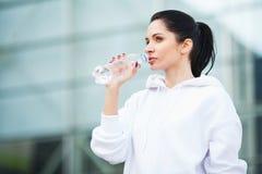 健身 体育和健康生活方式概念-在行使以后的妇女饮用水在公园 库存图片