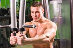 健身-做在健身房的强有力的肌肉人举重 库存照片