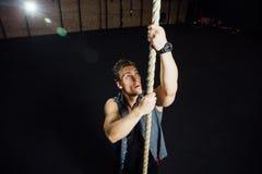 健身A男性运动员攀登在健身房的一条绳索 黑暗的背景,顶楼 库存照片