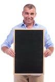 偶然中部拿着黑板的年迈的人 库存照片