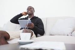 偶然人坐享受在他的片剂个人计算机的沙发音乐 库存照片