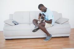偶然人坐弹有片剂个人计算机的沙发吉他 库存照片