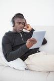 偶然人坐他的听到在片剂个人计算机的音乐的沙发 免版税库存图片