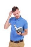 年轻偶然人拿着书并且认为 免版税库存照片
