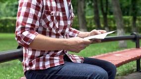 偶然人读书报纸在公园,消费悠闲时间,无忧无虑的周末 免版税库存图片