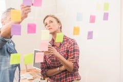 偶然企业同事与稠粘的笔记一起使用 免版税图库摄影